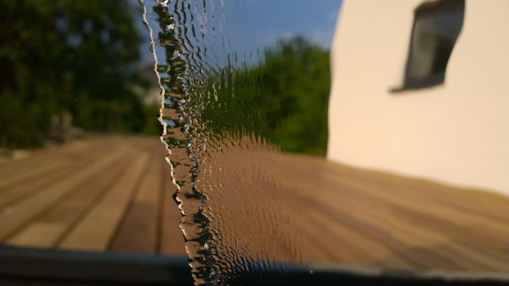 Blick durch die Wasserwand auf die Holzterrasse